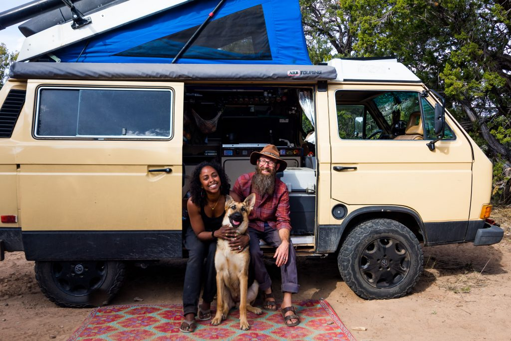 A couple poses with their German Shepherd dog in the door of a campervan