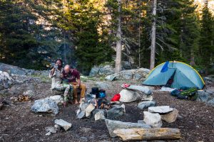 Noami & Dustin sit side by side on a log sharing a meal around a campfire. A tent is setup just in view.
