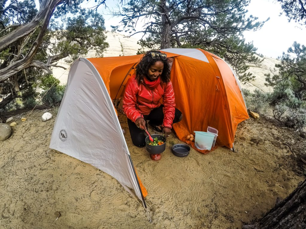 Noami crouches in the vestibule of her tent preparing a veggie stir-fry in a small pot atop a camp stove.