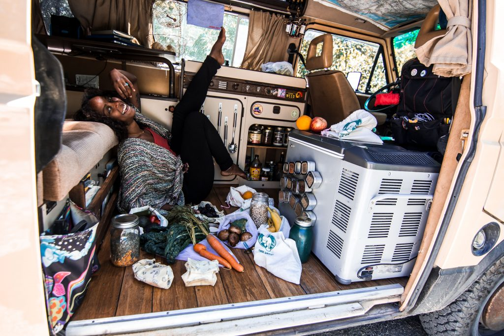 Noami lounges on the floor of her van smiling, surrounded by produce, reusable grocery bags and mason jars.