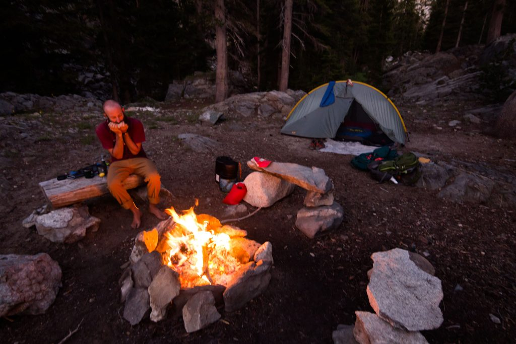 Dustin sits beside a campfire playing a harmonica. A tent and backpacks sit a safe distance away.