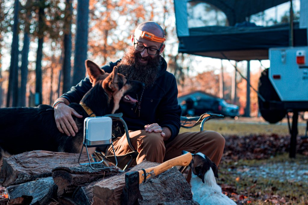 Dustin sits in camp chair petting Amara the German Shepherd dog. Dustin is wearing a rechargeable headlamp.