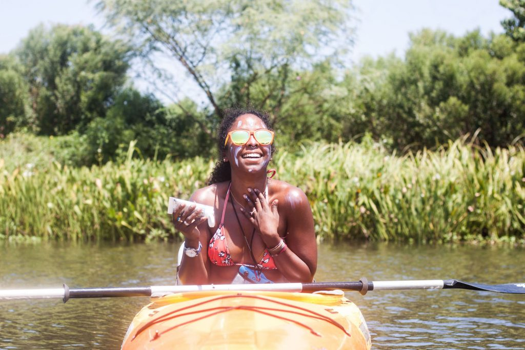 Noami sits in a canoe on the water applying eco friendly sunblock to her face.