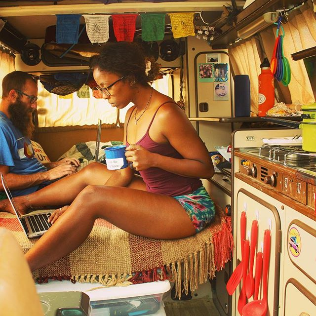 Dustin and Noami work on their laptops while sitting across from each other on the bed in the van. Noami drinks a cup of coffee