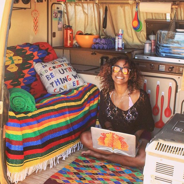 Noami sits on the floor of her van with the door open smiling and working on her laptop