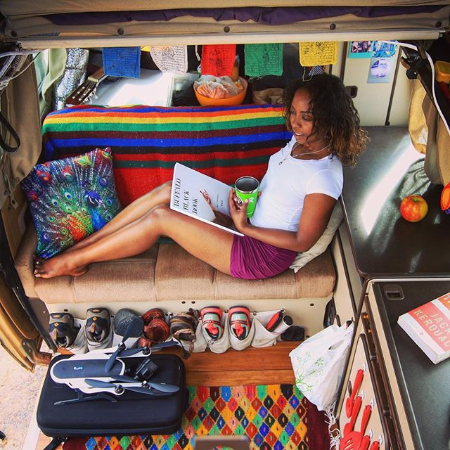 Noami sits in her van with her legs up on the bench seat staring outside and smiling while holding a closed book and cup.