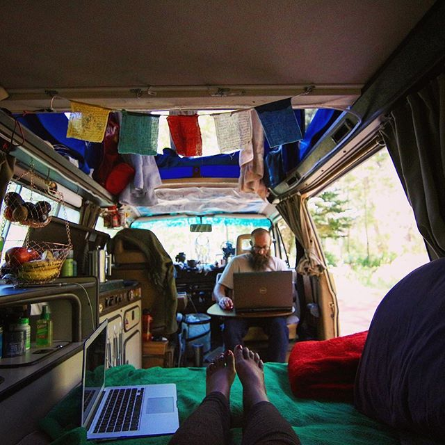 Dustin works on his laptop inside the van while Noami's laptop rests beside her feet on the bed.