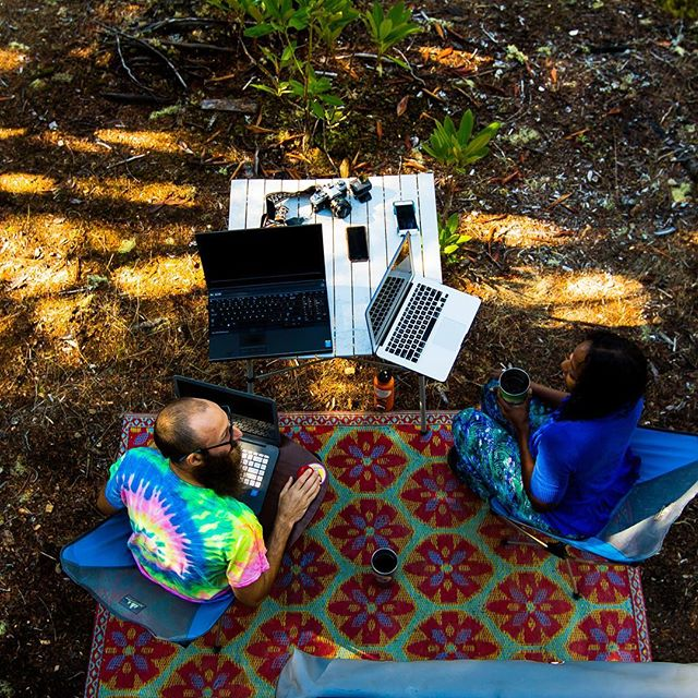 An aerial photo of Dustin and Noami working on their laptops outside their van camped out in nature.