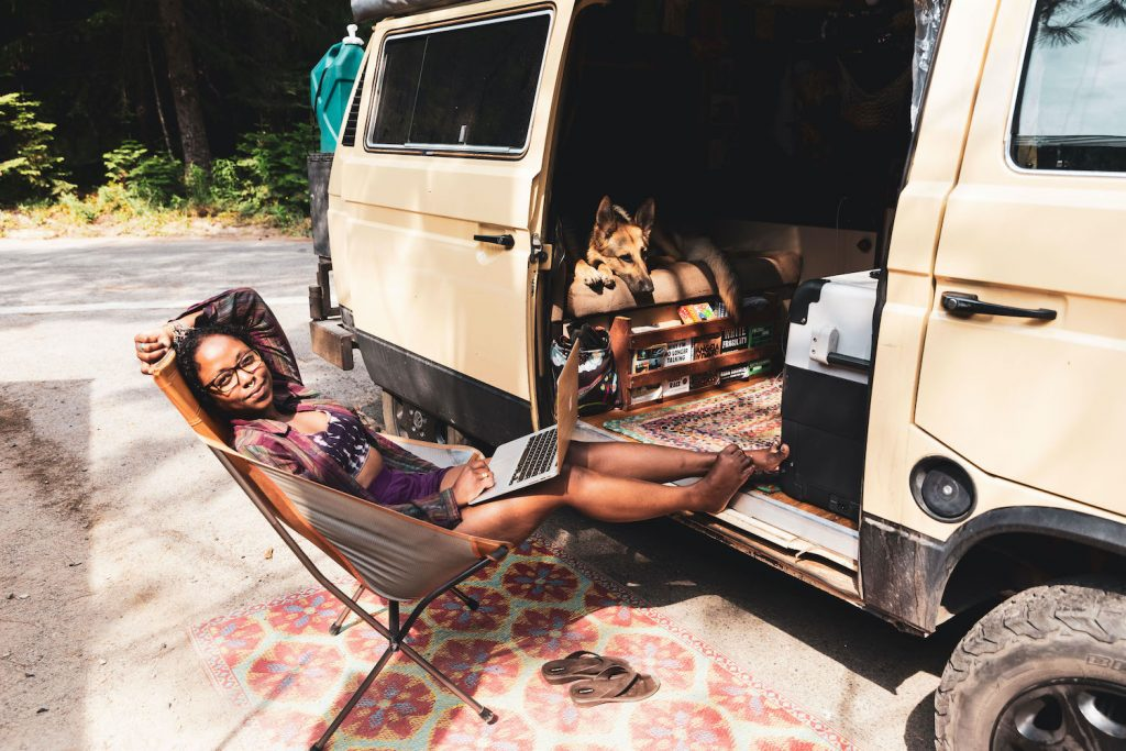 Noami sitting in a camp chair in front of her van smiling while working on her laptop. Her pup Amara is laying inside the van