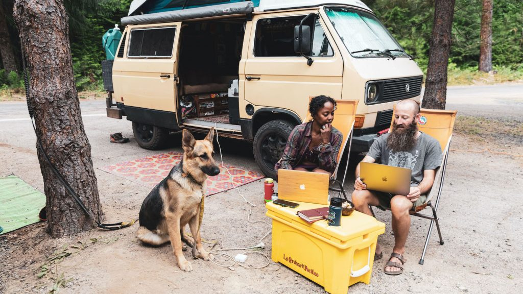 Digital nomads Dustin and Noami work at a campground on their laptops outside of their van, they use a yellow cooler as a desk. Amara the pup sits and stares.