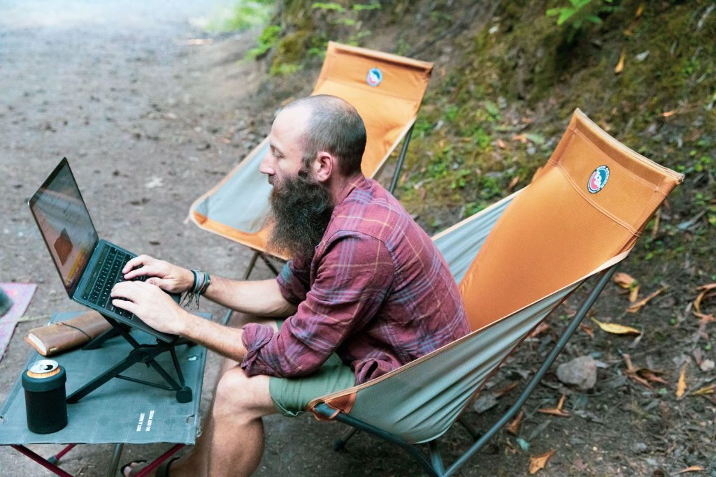 Dustin sits on a camp chair while working remotely on his laptop which sits on a laptop stand.