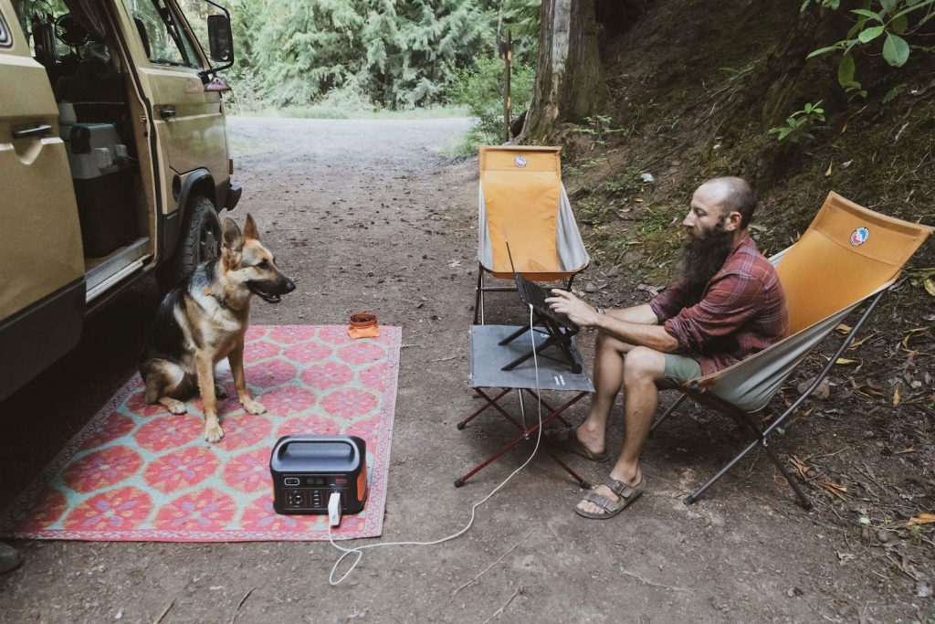 Dustin sits on a camp chair outside of his van working on his laptop. He is charging his laptop on a Jackery charging station. Amara, the German Shepherd dog, sits on a mat across from him.