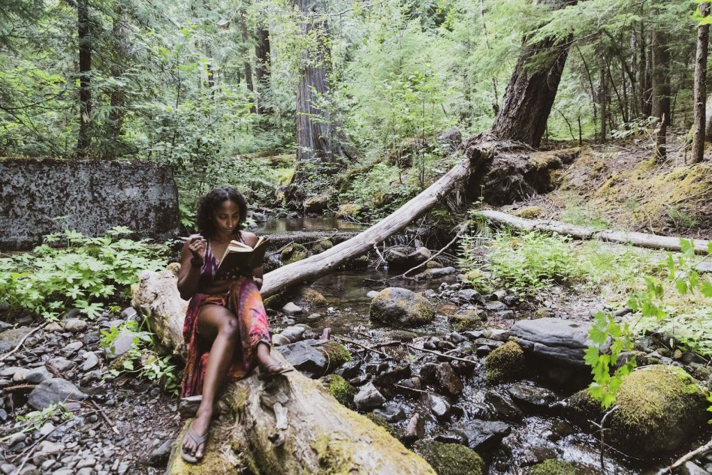 Noami is sitting in a forest on a log next to a rushing creek writing in her journal.