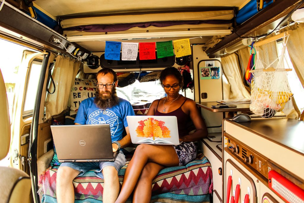 Digital nomads Noami and Dustin sitting in their van working on their laptops.