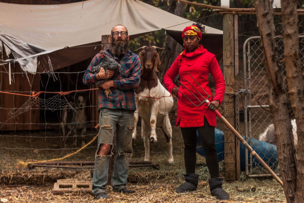 Dustin is holding a chicken and Noami is holding a pitchfork while a goat stands on his hind legs on the fence.