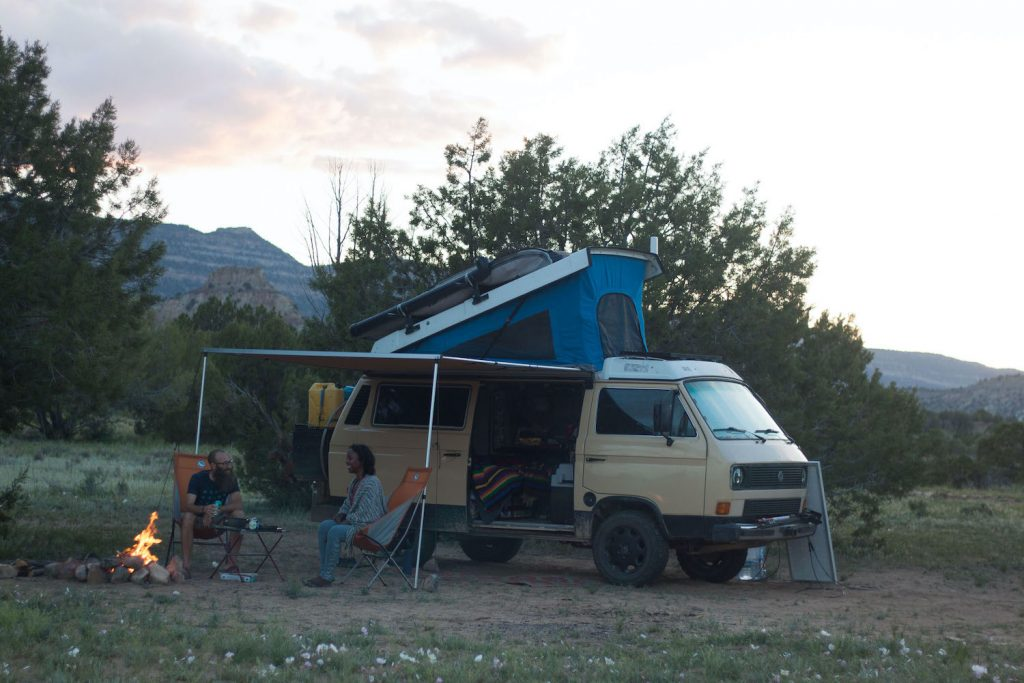 Dustin and Noami sitting in camp chairs around a campfire. The van is parked with the top popped and the awning out.