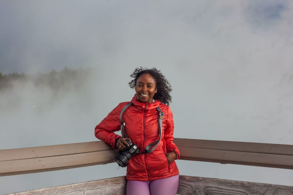 Noami stands on a boardwalk holding her camera. Steam from a geyser billows behind her.